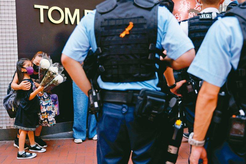香港一日晚發生刺警凶嫌自殘身亡,連日陸續有民眾持花到現場悼念凶嫌,圖為一名母親攜其女兒持花到現場,警方一旁戒備。 路透資料照片