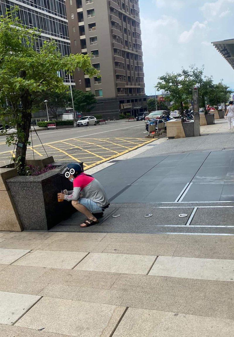 一名外送員趁著空檔休息時,蹲在一處水泥花台後用餐,讓網友們看了相當不捨。 圖/翻攝自「台中人大小事」臉書