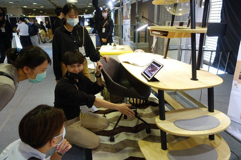樹德科大學生吳宗哲與(右二)張瑀庭(右一)在畢製專題展時為觀眾解說人貓共融書桌。圖/樹德科大提供