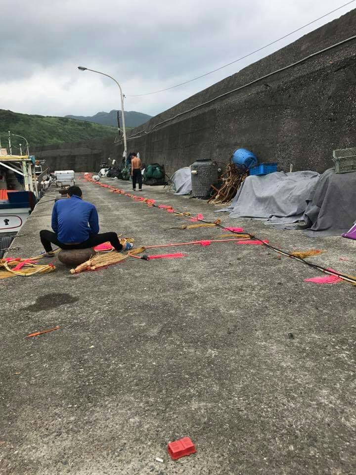 漁民在休息時於港邊整補驅趕繩。圖/新北市漁業處提供