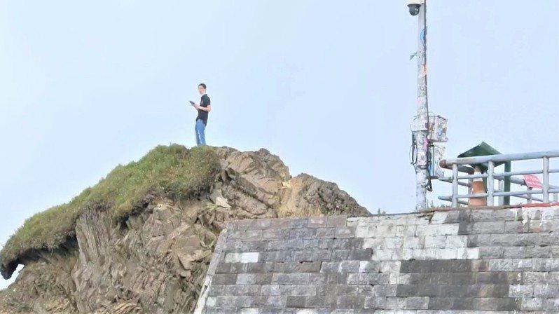 合歡山地區今人潮明顯變多,因地標「武嶺亭」封閉,竟有民眾為拍照取景攀爬岩石登高。圖/讀者提供