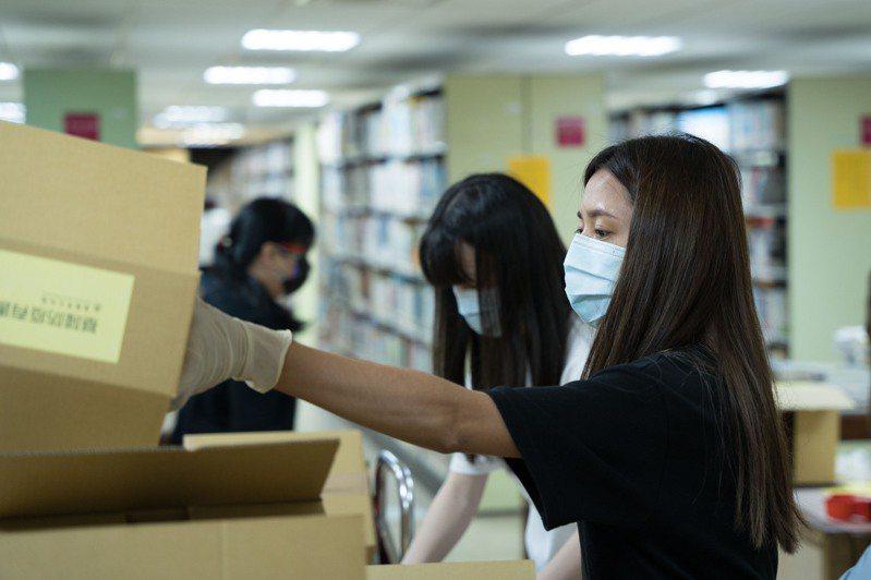 基隆市文化局舉辦「基隆防疫有書香」活動,文化局同仁撿書、裝箱展現高效率。圖/基市府提供
