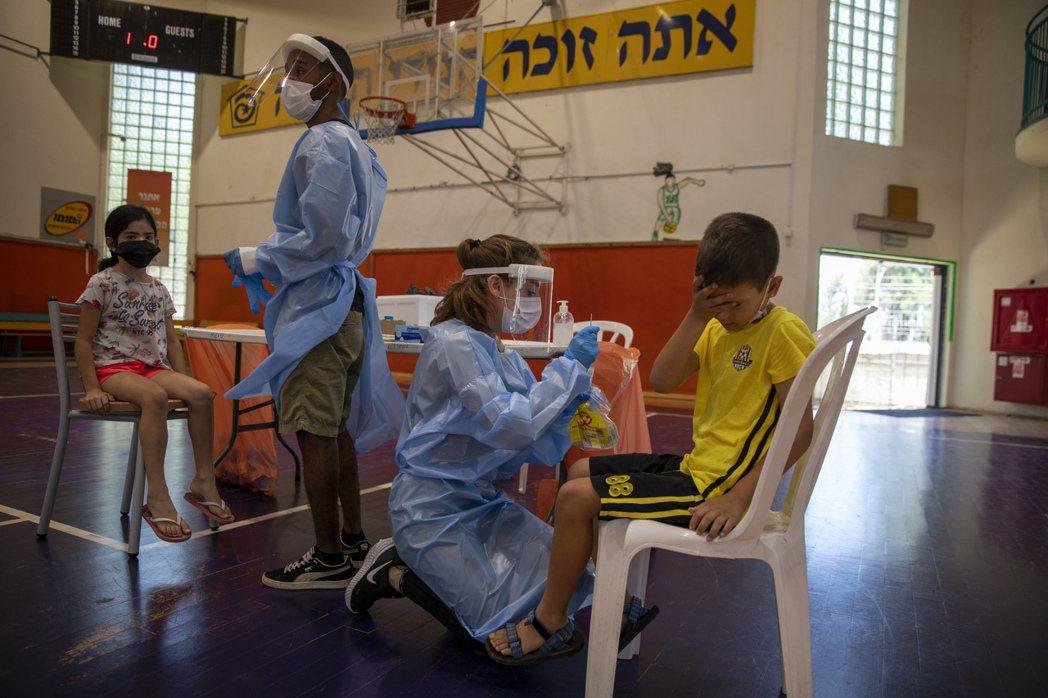 以色列總理日前敦促年輕人接種疫苗,圖為醫護人員為兒童進行病毒檢測。 圖/美聯社