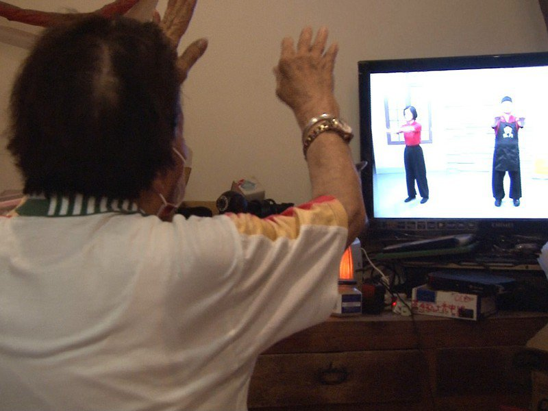 平溪區嶺腳關懷據點運用公用頻道早上八點「防疫動健康」課程,讓平溪的老人家們能跟著電視天天活動一下。 圖/觀天下有線電視提供