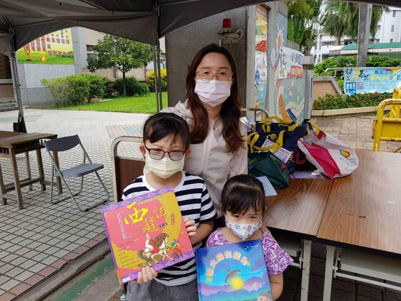 嘉市嘉北國小推出1袋10本書的「外帶閱讀全家餐」,圖為許姓家長帶孩子來借。圖/嘉北國小提供