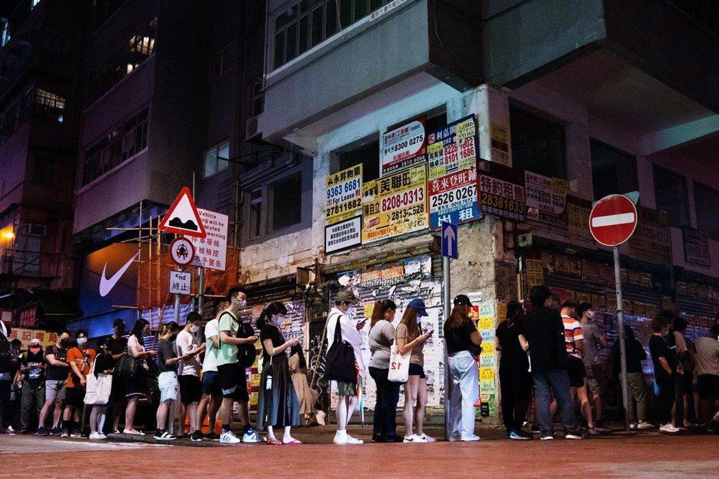6月24日,人們在旺角一處報攤排隊等著購買第一批印好的《蘋果日報》。 圖/法新社...