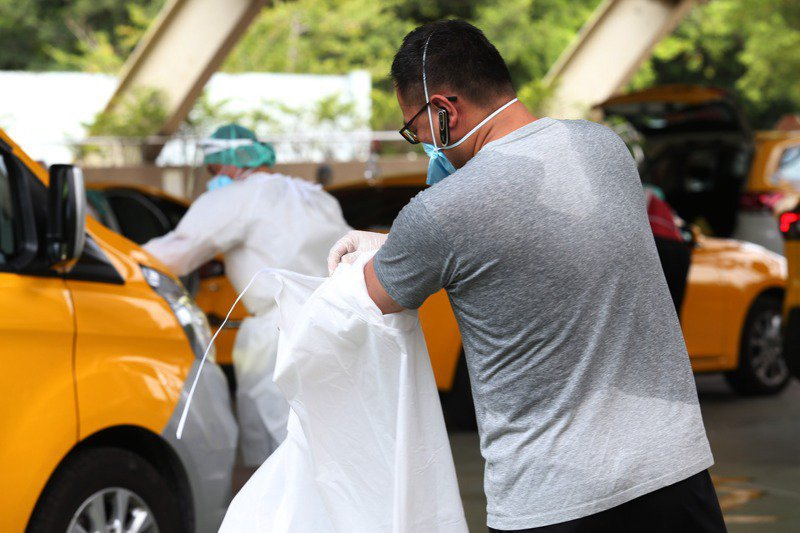疫災嚴峻時,來自民間的自發性互助與關懷,從內部凝聚台灣社會繼續向前走。圖為防疫司機脫下防護衣滿身大汗。圖/聯合報系資料照片