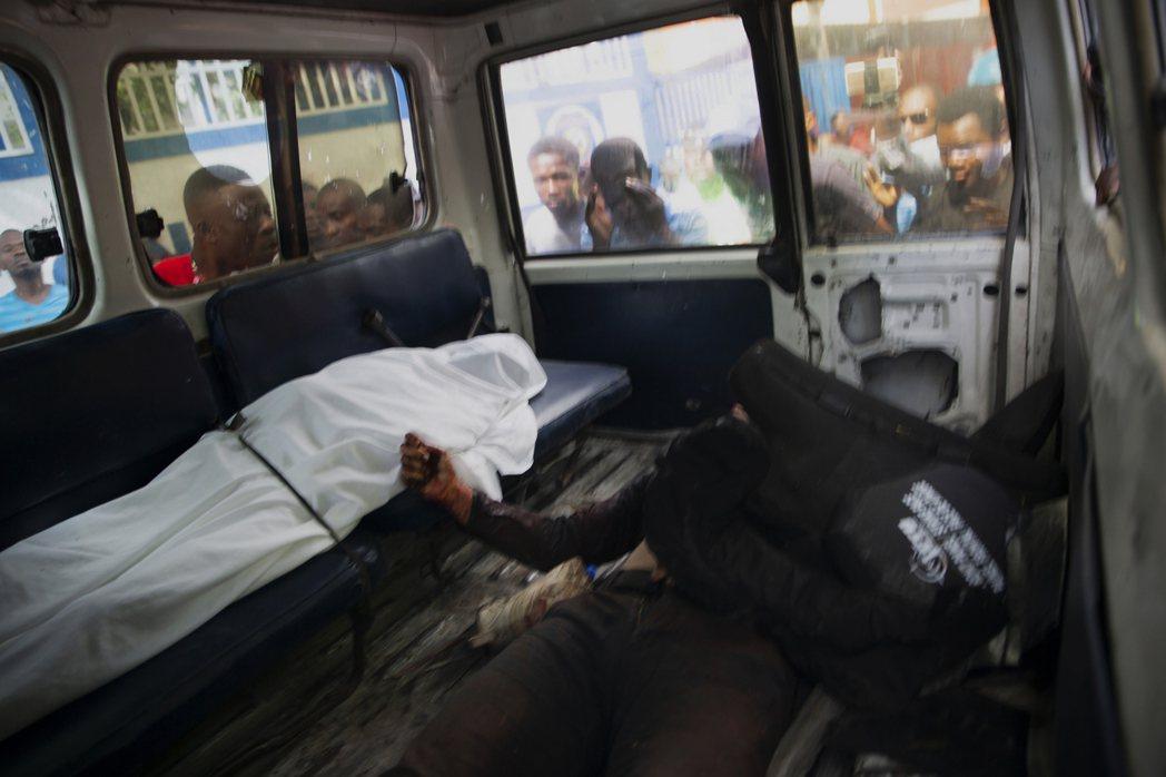 民眾圍觀車內在槍戰中喪生的嫌犯。 圖/美聯社