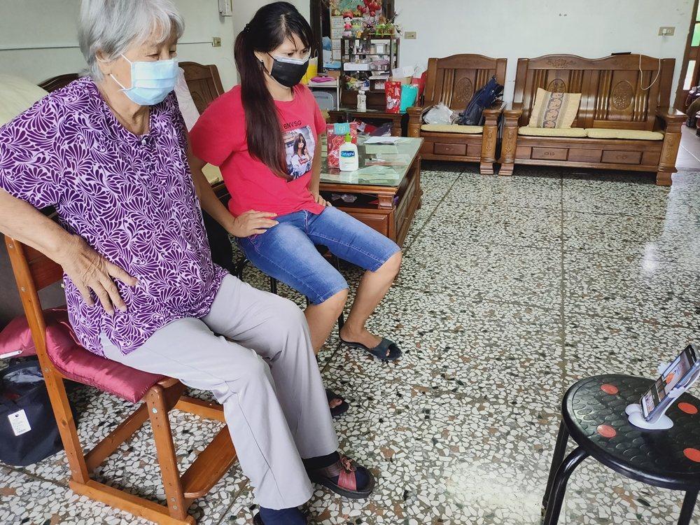 85歲的阿伸阿嬤,在「外籍看護」神隊友協助下與弘道社工遠距進行視訊運動。 圖/弘...