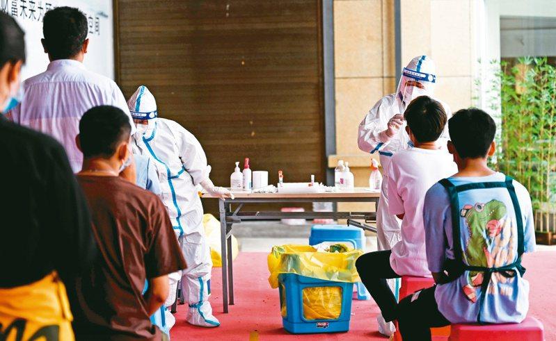 圖為大陸雲南防疫人員為當地民眾進行核酸檢測。新華社