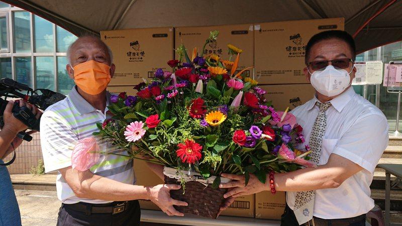 彰化縣田尾鄉長林守政(左)贈送鮮花給「健康天使」負責人盧科源,感謝他捐贈醫療級口罩。記者簡慧珍/攝影