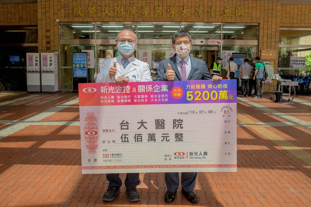新光人壽總經理黃敏義(右)代表致贈500萬元防疫基金,由台大醫院院長吳明賢(左)...