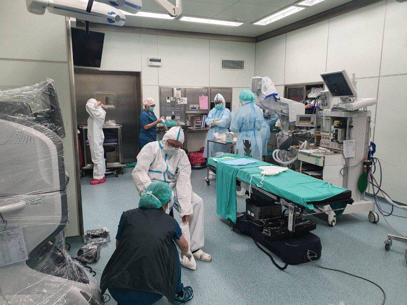 醫護團隊穿全套防護衣,戴3層手套、防護面罩、隔離護目鏡,施行顯微鏡手術確實吃力。圖/台中慈濟醫院提供