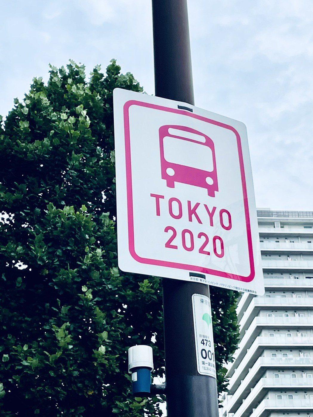 東京新增的路標,白底配上粉紅色畫了一台巴士,寫著「TOKYO 2020」。圖/張...