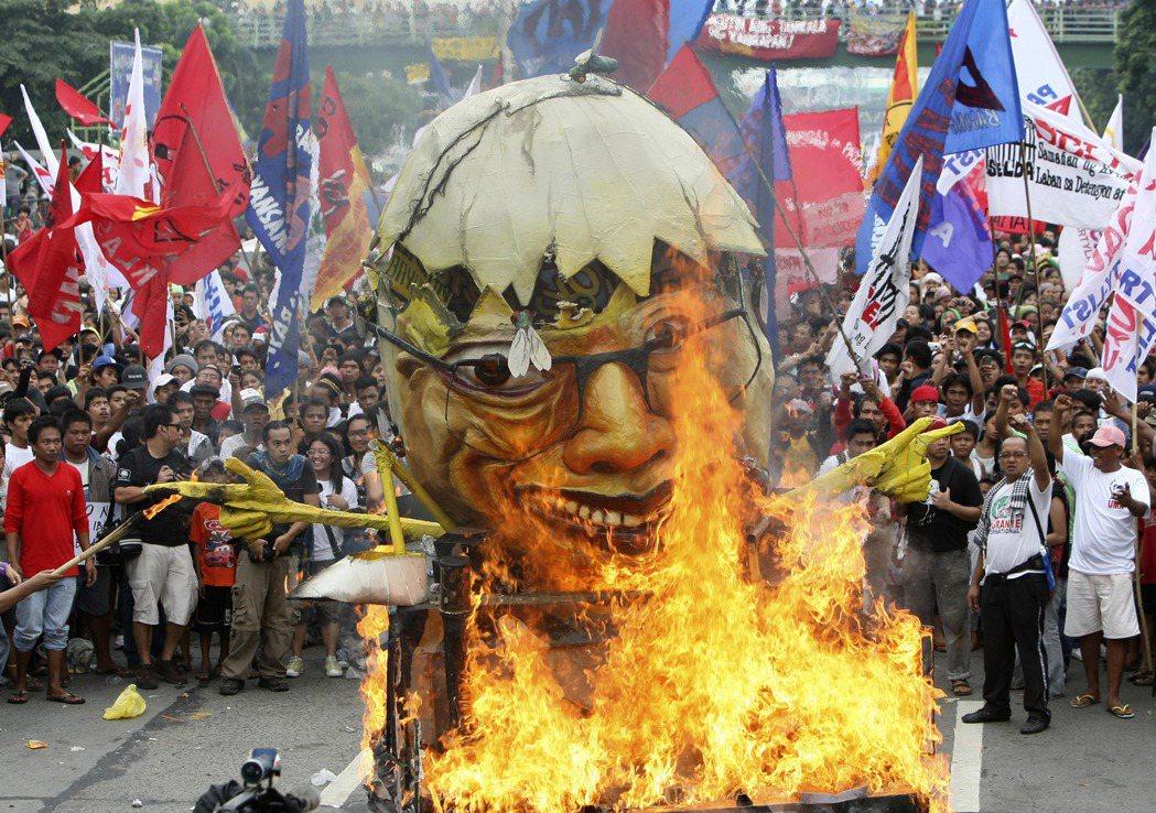 2011年,菲律賓環境議題倡議者在馬尼拉抗議艾奎諾,焚燒其惡搞肖像。 圖/美聯社...