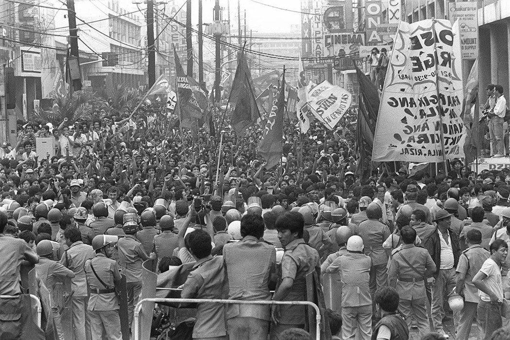 1985年9月21日,菲律賓民眾上街抗議,與在馬尼拉總統府前的防暴警察對峙。...