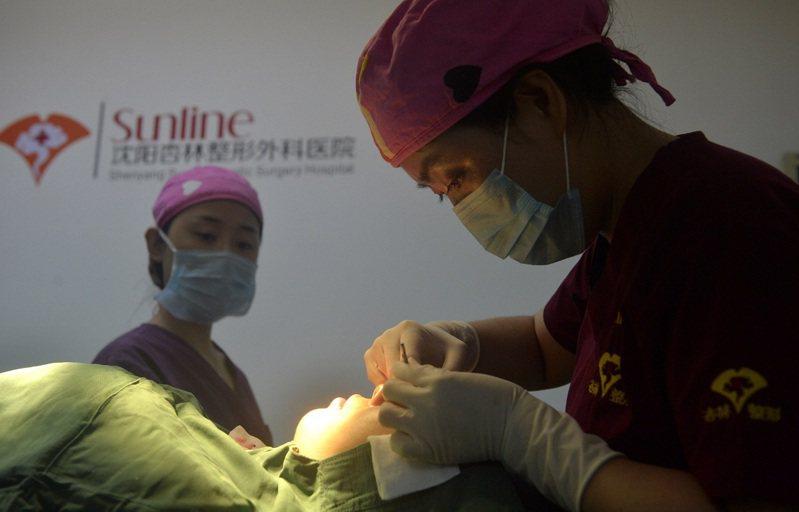 中國大陸遼寧省瀋陽市一位醫師正為一位女大學畢業生動眼部醫美手術。中國大陸民間對整型手術的態度正在產生變化,1996年後出生的Z世代已不視整容為一種忌諱。路透/Oriental Image