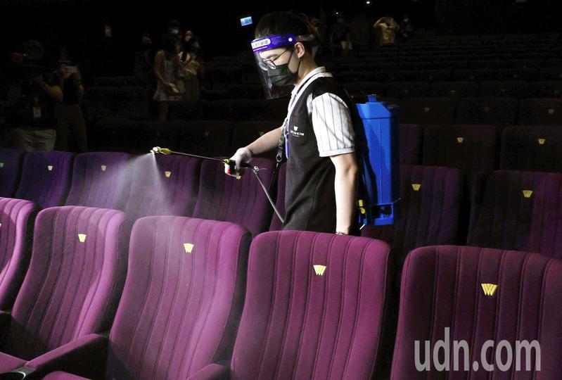 三級警戒後的微解封首日,戲院在遵守防疫規範下重新營業,業者在每一場次結束後,安排工作人員清消。記者侯永全/攝影