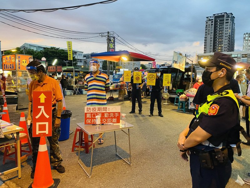 台南市北區新成功夜市今晚復業,員警持海報加強宣導防疫。圖/台南市警五分局提供