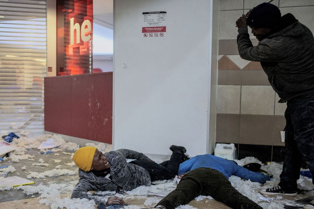 一名商店老闆正毆打疑似洗劫商店的示威者。 圖 / 法新社