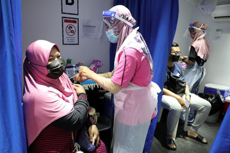 吉隆坡民眾12日接種新冠疫苗。路透