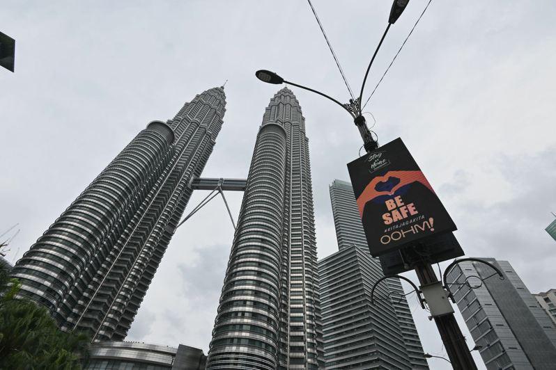 在馬來西亞吉隆坡的馬來西亞國家石油公司雙塔前,一塊屏幕提示人們保持健康。 新華社