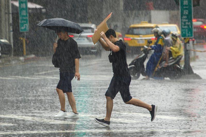 圖為民眾拿紙版遮雨。中央社資料照