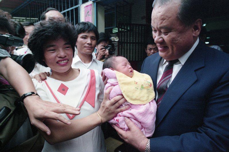 內政部以公開抽籤方式,抽出沈燕禎為台灣地區第2000萬名國民,內政部長許水德(右)前往祝賀。圖/聯合報系資料照片