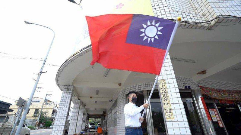 前立委顏寬恒在他和妹妹顏莉敏沙鹿服務處前揮舞國旗。圖/取自顏寬恒臉書
