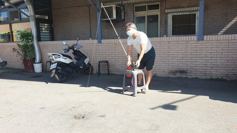 新北市瑞芳區深澳路林姓男子從路面洩水孔洞,釣到1斤半的鰻魚,影片上傳網路形成話題。記者邱瑞杰/攝影