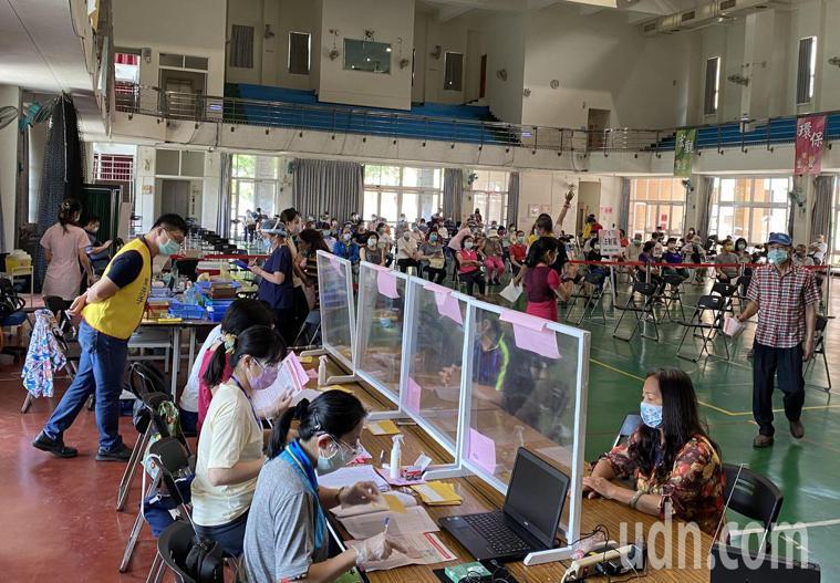 台中市長者今天到南屯惠文國小快打站接種莫德納疫苗,接種前工作人員詢問「有沒有打過...