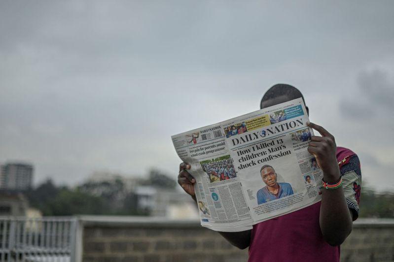 肯亞一名男子15日閱讀頭版刊登5年內殺害至少10名青少年的男子萬賈拉報紙。法新社