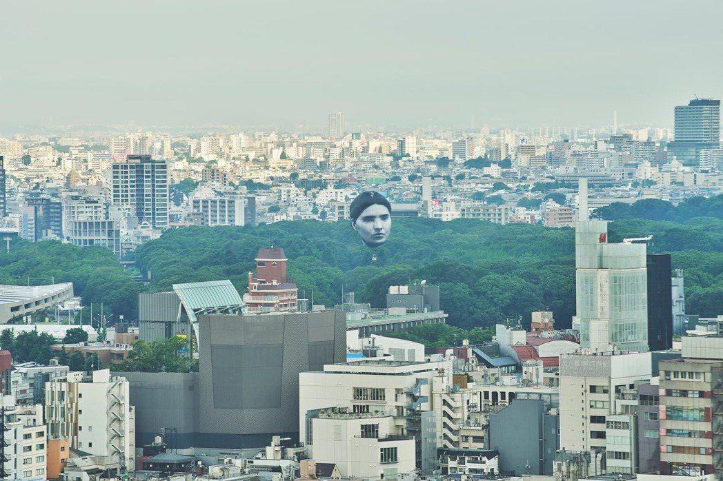 由藝術家荒神明香創作的「正夢」作品,以巨大男性人臉氣球,飄浮在東京上空。圖/翻攝...
