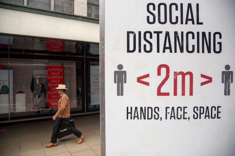 圖為英國倫敦一名男子從提示人們保持社交距離的牌子旁走過。新華社