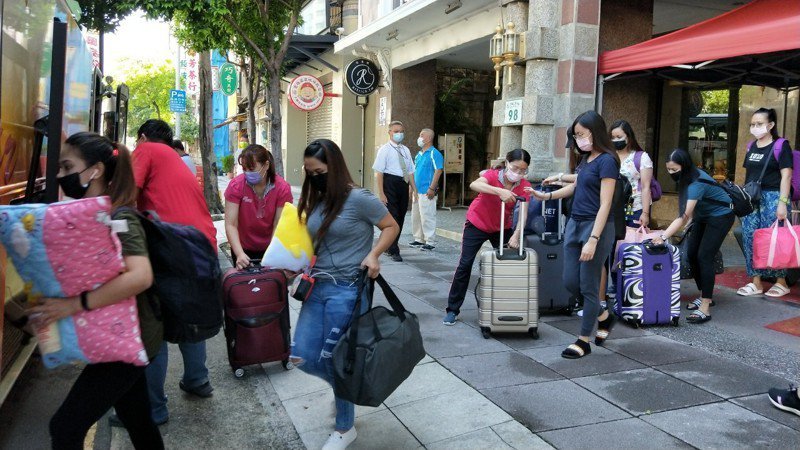 140名日月光員工今天離開高雄漢王飯店,飯店員工協助將行李送上大巴。圖/高雄漢王飯店提供