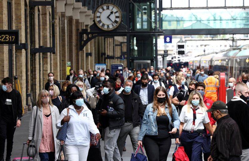 英國單日新增新冠病例近期持續攀升,16日新增逾5萬例。圖為12日倫敦國王十字車站月台上的旅客。(路透)