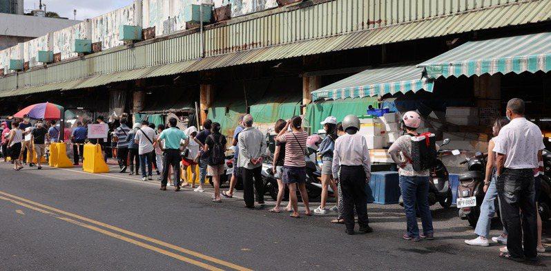 微解封的首個假日,位於南方澳的南寧魚市湧入人潮,市場方遵照防疫指引,消毒、量測體溫、實名制並限制人流,大批民眾排隊等待進入。記者許正宏/攝影