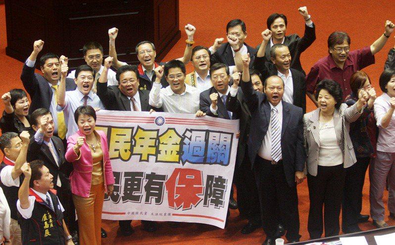 2008年7月18日,立法院三讀通過國民年金法修正案,國民黨立委拿著海報高興慶祝「國民年金過關,全民更有保障」。圖/聯合報系資料照片