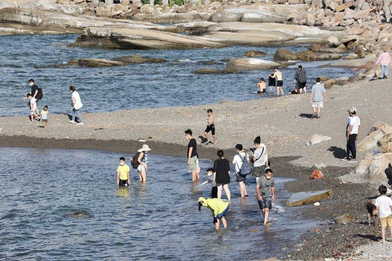 疫情趨緩微解封,首個假日的基隆潮境公園人潮湧現,不少悶壞了的遊客出門透氣散心,海邊滿滿都是戲水人潮。記者許正宏/攝影