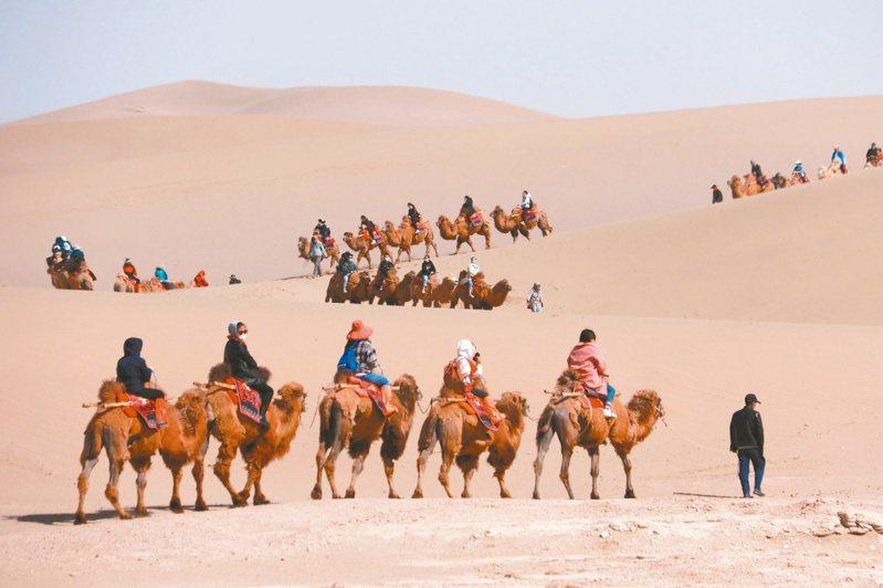 甘肅敦煌進入旅遊「特旺季」,圖為遊客在甘肅省敦煌市鳴沙山月牙泉景區遊覽。(新華社)