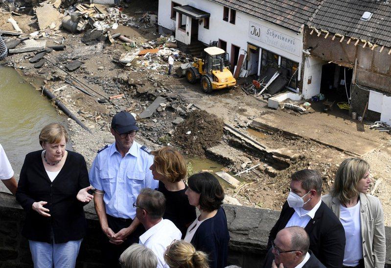 德國總理梅克爾(左)十八日到萊因法耳次邦舒爾德村水患災區勘災。(美聯社)