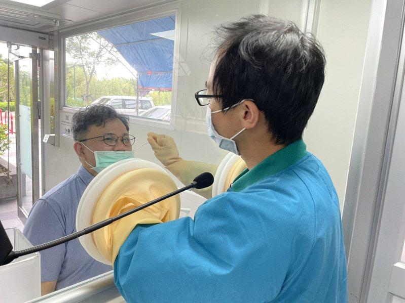 醫師透過採檢窗幫民眾採檢,採檢棒由自動轉液系統收回,完成後續的試劑添加及檢測。記者陳斯穎/攝影