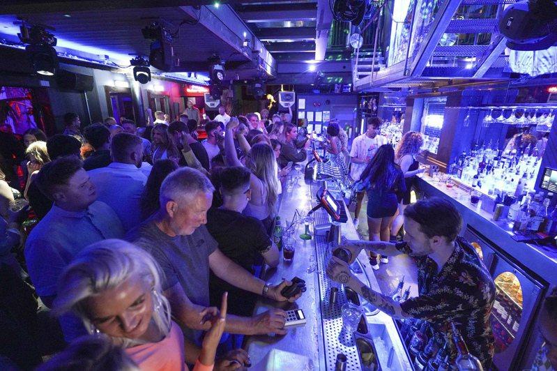 英國19日全面解封,18日午夜12時一過,各地酒吧就擠爆。圖為里茲一家酒吧的盛況。 美聯社