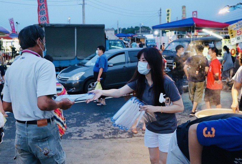 昨天晚間嘉義縣大林夜市恢復營業,縣農會總幹事黃貞瑜在入口處分送民眾防護面罩。圖/黃貞瑜提供