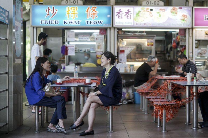 新加坡6月21日開放每組最多兩人內用後,美食區商家用網子將座位隔開。(歐新社)