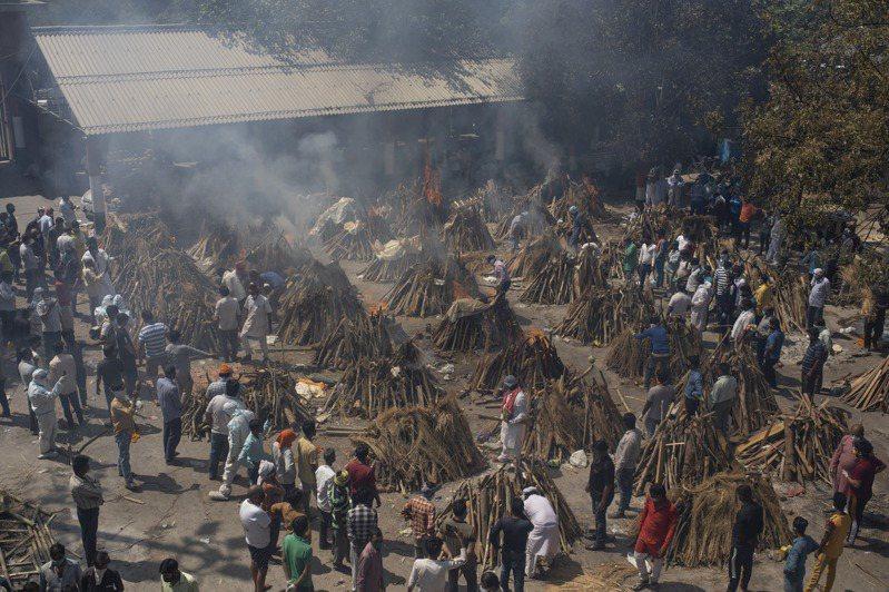 印度4到5月疫情嚴重,新德里一個火葬場4月24日堆起許多火葬堆,將新冠肺炎死者遺體火化。(美聯社)