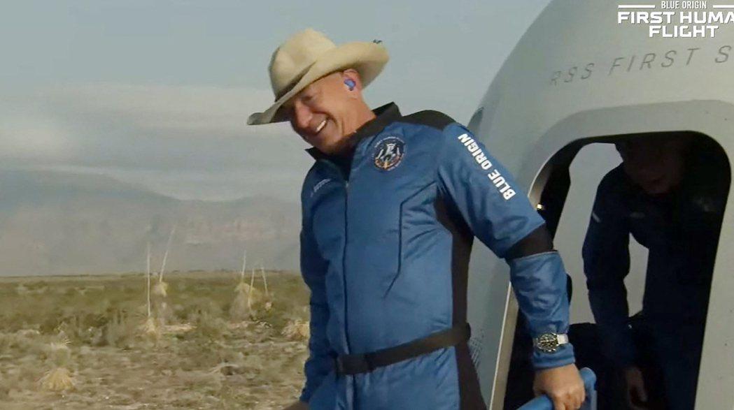 亞馬遜創辦人貝佐斯20日完成太空之旅降落地面後,開心地走出太空船。(法新社)