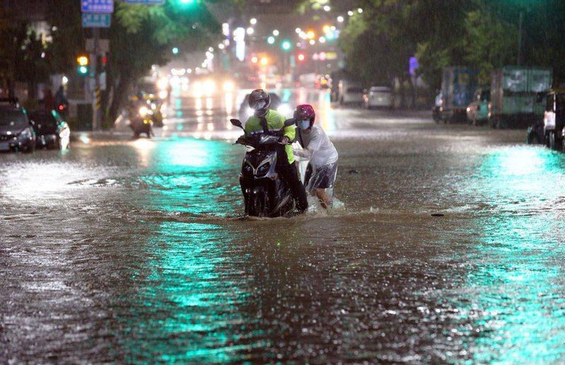 高雄市昨晚降下大雨,持續雨勢加上不時閃爍的閃電聲響十分驚人,鼓山路附近淹水,機車進水故障只能推車前進。記者劉學聖/攝影