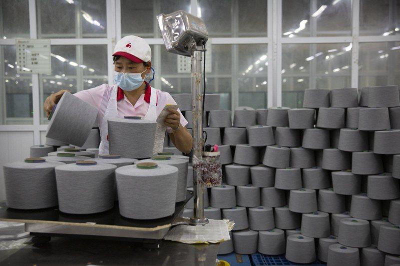 新疆維吾爾族自治區內,一家工廠員工正整理棉線軸。  美聯社