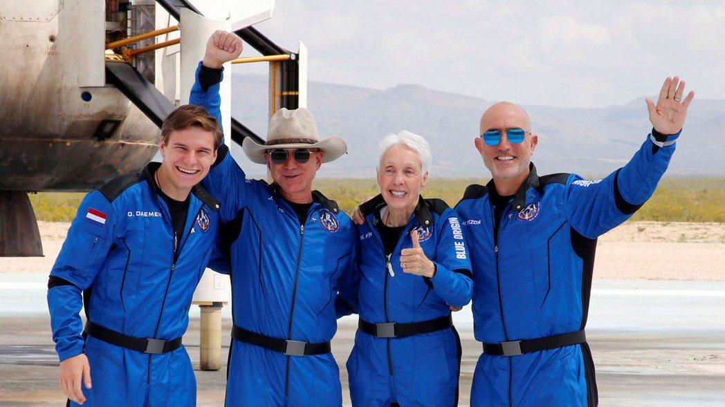 貝佐斯(左二)在成功降落後,和其他三名乘客一起開心地合影。圖/路透